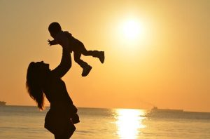 Frau hebt Kind hoch, das in ihrem Leben am wichtigsten ist