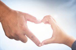 Die Hände von Vater und Kind formen ein Herz, sie sind Superhelden im Kampf gegen Krebs