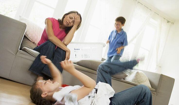 Vollzeitmutter - Kinder spielen und Mutter ist verzweifelt
