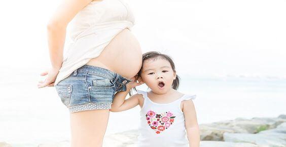 Planung einer zweiten Schwangerschaft - Schwangere Frau mit Tochter