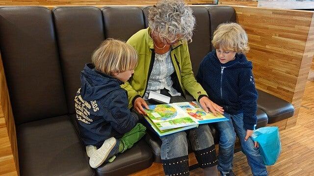 Großeltern lesen ein Buch vor