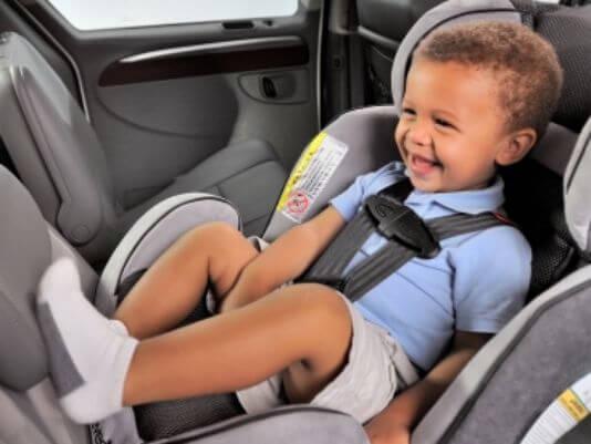 Kind sitzt lachend ohne Winterjacke im Kindersitz