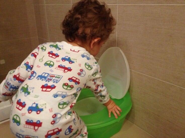 Kind übt mit dem Töpfchen die Windelentwöhnung