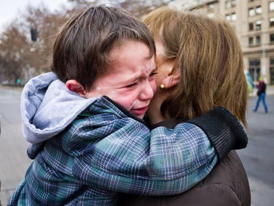 Zu verabschieden - Junge weint in Mamas Armen