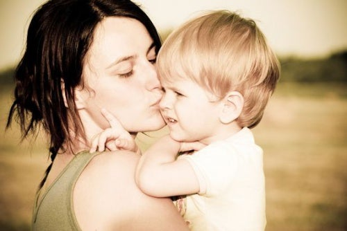 Mutter schreit nicht, küsst Kind auf dem Arm auf die Wange