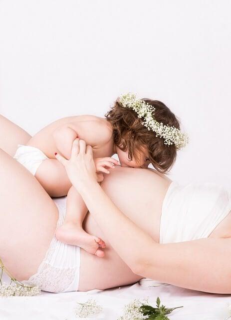 Kind küsst schwangeren Bauch für Pränatale Stimulation