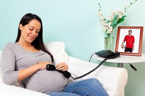 Schwangere telefoniert mit Ungeborenem für pränatale Stimulation