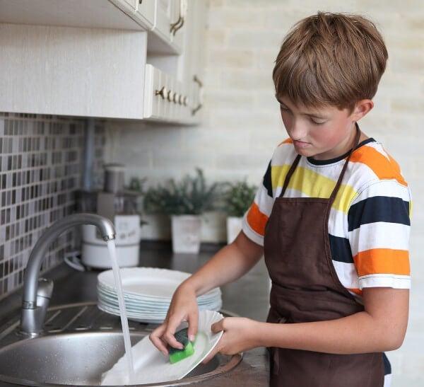 dein Zuhause sauber halten - Junge spühlt Geschirr