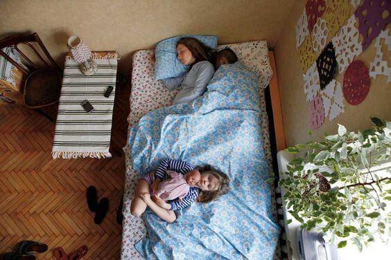 Kinder wollen häufig mit im Elternbett schlafen. Ein Faktor der die Müdigkeit der Eltern beeinflussen kann.