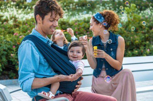 Vater und Mutter mit Kind in Babytrage