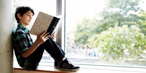 gute Lerngewohnheiten - junge-liest-am-fenster-als-gute-lerngewohnheit