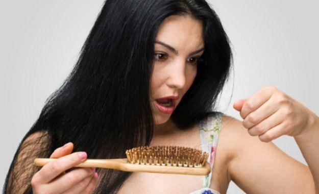 Frau reagiert mit Entsetzen auf den Haarausfall nach der Geburt