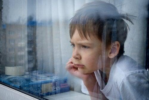 Kind mit Kinderfrustration schaut aus dem Fenster.