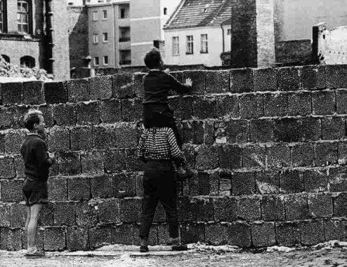guter Vater mit Kindern vor Mauer