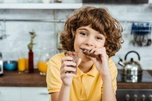 Kind isst Schokolade, um die intellektuelle Leistung zu stärken