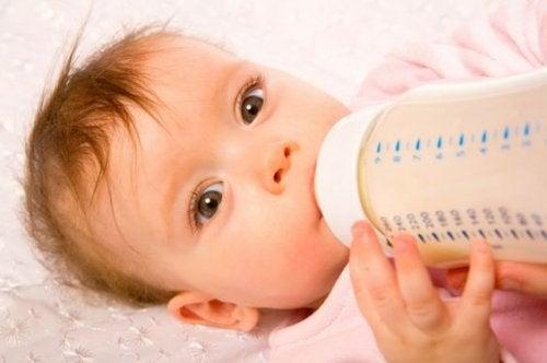 Das Baby trinkt aus der Flasche, um sich langsam von der Brust zu entwöhnen.