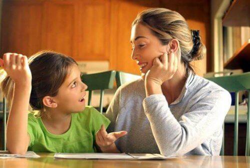 Die Mutter redet mit ihrem Kind zusammen am Tisch, um die Disziplinierung ihres Kindes zu erreichen.
