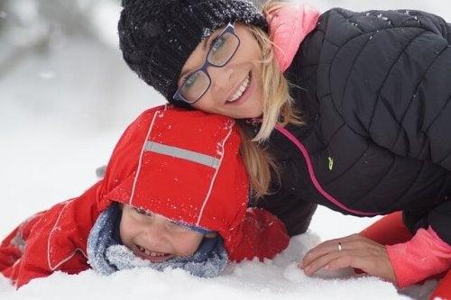 Mutter und Kind lachen im Schnee