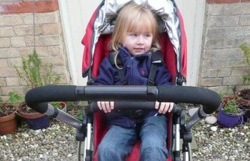 Kleines Mädchen sitzt in Kinderwagen.