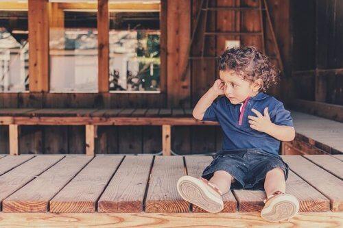 Kleiner Junge sitzt weinend auf einem Holzsteg.