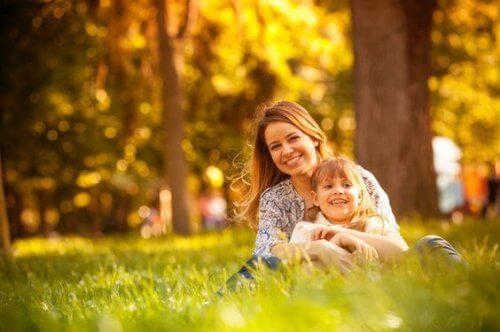 Mutter sitzt mit Kind im Park.