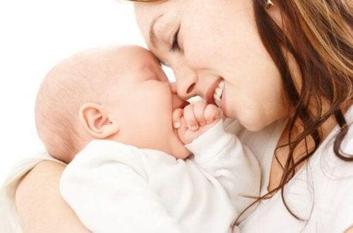 Mutter hält Baby im Arm und beide lachen.