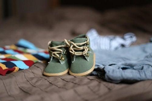 Kleine Babyschuhe liegen auf Klamotten.