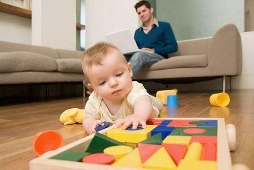 Baby spielt mit Bauklötzen, damit die Sinne stimuliert werden.