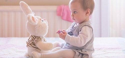 Baby spielt mit Plüschhase.