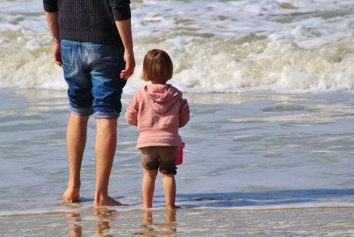 Vater steht neben Tochter am Strand.