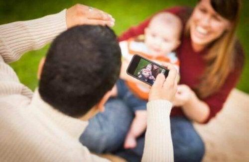 Vater macht ein Handybild von seinem Baby.