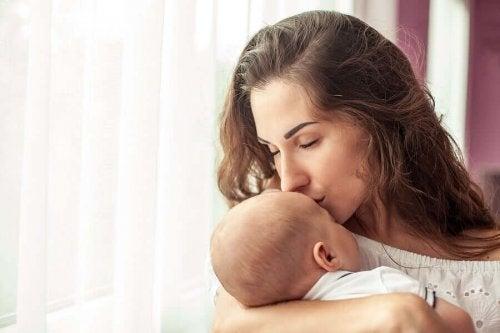 Wochenbett: Mutter küsst Baby am Fenster
