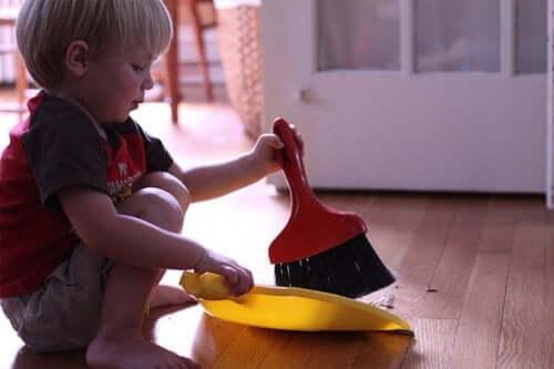 Im Haushalt helfen: Kind mit Handbesen und Kehrichtschaufel