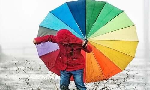 Kind mit buntem Regenschirm