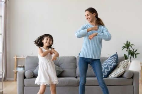 Kinderbetreuung: Mädchen und Kinderfrau tanzen vor dem Sofa