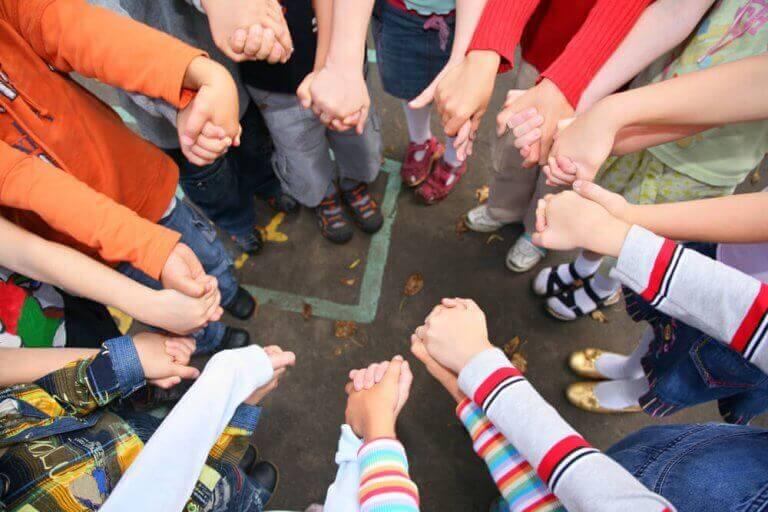 Sozialisation - eine Gruppe von Kindern hält sich an den Händen