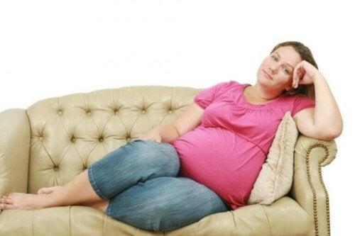 Polytrauma - schwangere Frau auf dem Sofa