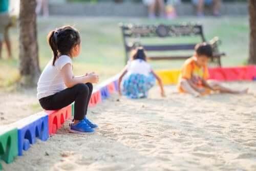 Freunde - Kind sitzt alleine am Sandkasten