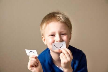 Junge spielt mit Papiermund
