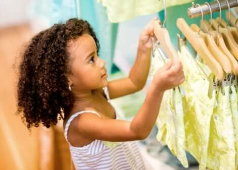 Kleines Mädchen betrachtet Kleider