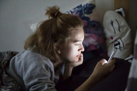 Mädchen mit Handy in Kontakt mit anderen Jugendlichen