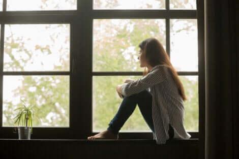 Mädchen sitzt am Fenster und blickt hinaus